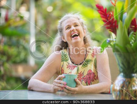 Joyful Senior Woman Laughing stock photo, Joyful senior aged woman with mug laughing outdoors by Scott Griessel