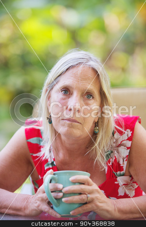 Attractive Woman on Vacation stock photo, Sympathetic middle aged Caucasian female holding a coffee up by Scott Griessel
