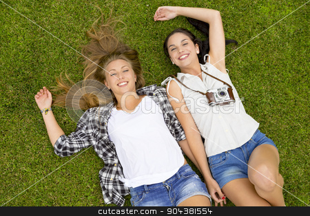 Best Friends stock photo, Female best Friends lying on the grass and having a good time together by ikostudio