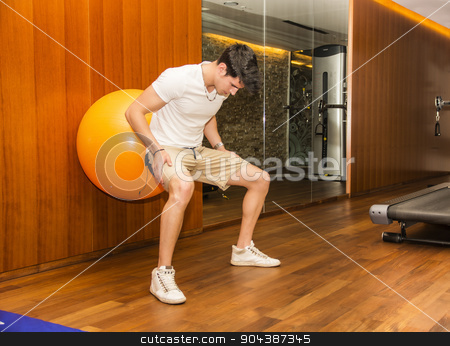 Handsome young man working out at gym stock photo, Attractive young man working out with exercize ball against wall to train abs by Stefano Cavoretto