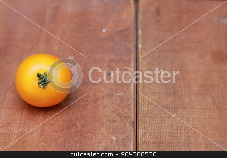 Single yellow cherry tomato on wood background stock photo, Single yellow cherry tomato on wood background by Tara Huff