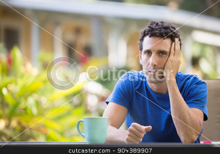 Tired Man in Tropical Outdoors stock photo, Tired man with hand on head sitting outdoors by Scott Griessel