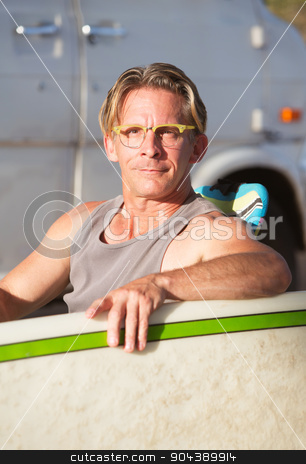 Cute Surfer with Surfboard stock photo, Cute middle aged surfer holding his surfboard by Scott Griessel