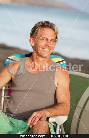 Close up of Smiling Man at Beach stock photo, Close up of happy male sitting on beach by Scott Griessel