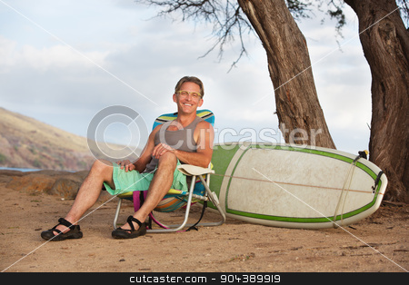 Smiling Man Sitting with Surfboard stock photo, Single cheerful athletic male sitting with surfboard by Scott Griessel