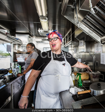 Female Chef on Food Truck stock photo, Chef with pink hair directs staff on food truck by Scott Griessel