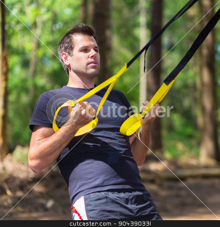 Training with fitness straps outdoors. stock photo, Young attractiveman does suspension training with fitness straps outdoors in the nature. by kasto