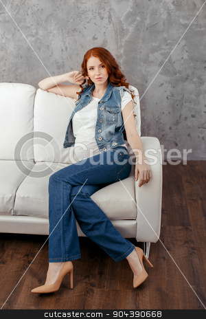 Pregnant woman relaxing at home looking very happy stock photo, Young attractive pregnant woman relaxing on the sofa  by Dmytro Buianskyi