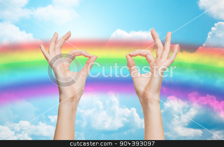 hands showing ok sign over rainbow background stock photo, people, gay pride, gesture and homosexual concept - human hands showing ok sign over rainbow in blue sky background by Syda Productions