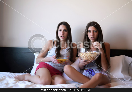 Best friends watching tv or a movie in bed stock photo, Two beautiful young women in bed watching a movie or tv, and eating popcorn and nachos. Scared expression. by nicolas menijes