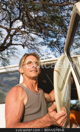 Independent Surfboarder stock photo, Athletic middle aged man with smile and surfboard by Scott Griessel