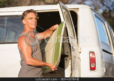 Man Removing Surfboard stock photo, Single handsome man removing surfboard from of his van by Scott Griessel