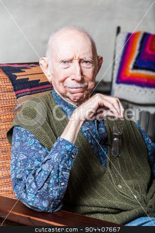 Elder Gentleman in Livingroom stock photo, Stern elder gentleman sitting on chair in livingroom by Scott Griessel