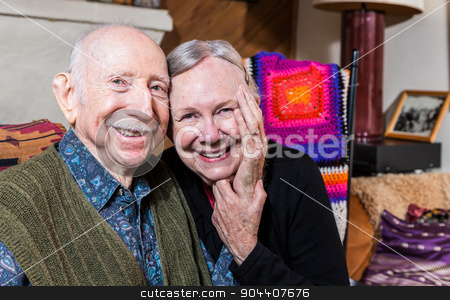 Happy Older Couple Sitting Together stock photo, Smiling couple sitting together in living-room touching hands by Scott Griessel