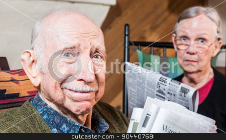 Elderly Man and Woman with Newspaper stock photo, Elderly man and woman with the newspaper indoors by Scott Griessel