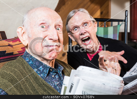 Old Mad Couple with Newspaper stock photo, Old mad couple reading a newspaper in their living-room by Scott Griessel