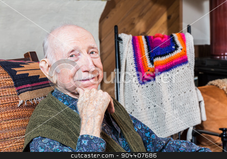 Older Smiling Gentleman Sitting stock photo, Older gentleman smiling and seated in his living-room by Scott Griessel