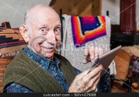 Elder Gentleman with Tablet stock photo, Elder gentleman working on a tablet in his living-room by Scott Griessel