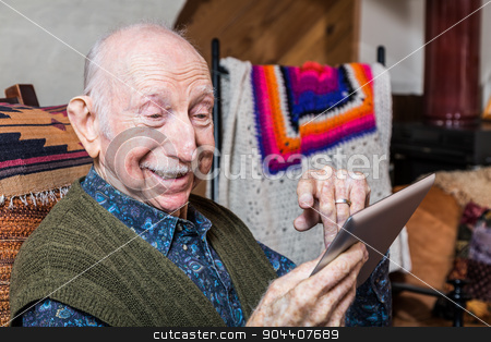 Smiling Older Gentleman with Tablet stock photo, Smiling older gentleman working on a tablet in his living-room by Scott Griessel