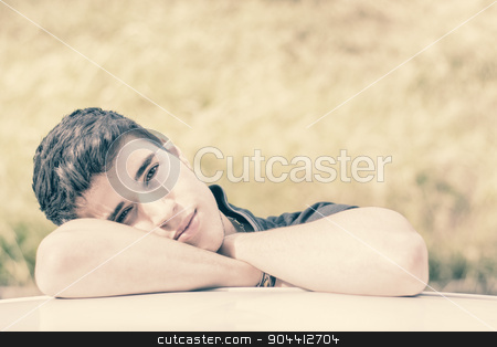 Young man looking at camera outdoor, leaning with head resting on hands stock photo, Head and arms shot of handsome attractive young man looking at camera outdoor, leaning on flat surface with head resting on hands by Stefano Cavoretto