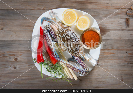 Raw blue crab and ingredients on plate stock photo, Above view raw blue crab and ingredients ready to cook, on white plate.  by szefei