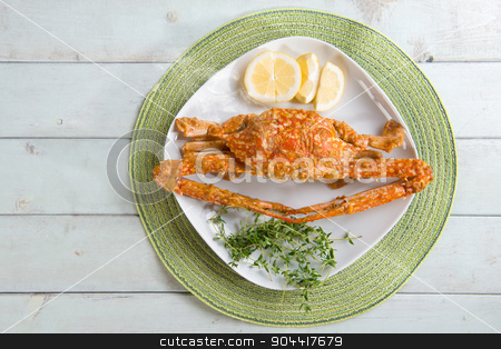 Delicious chili crab stock photo, Overhead view cooked delicious hot and spicy sauce blue crab on white plate, at bright wooden background. Fresh cook with hot smoke steams. by szefei