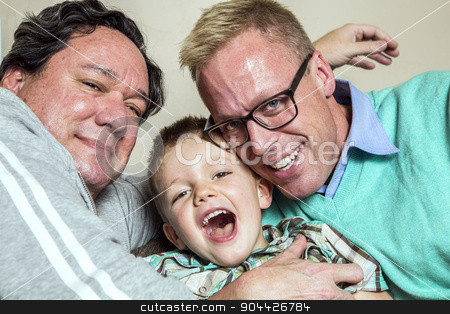 Gay Couple with Young Son stock photo, Two gay men hug their happy young son by Scott Griessel