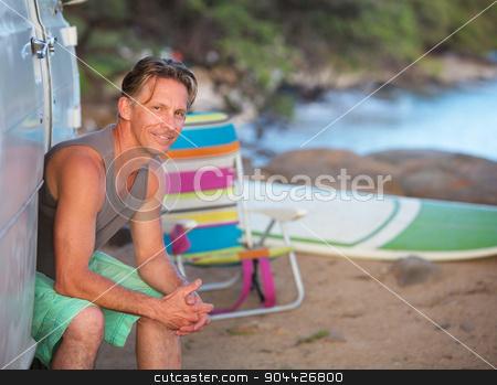 Happy Surfer Sitting at Beach stock photo, Male European surfer sitting in van door on beach by Scott Griessel