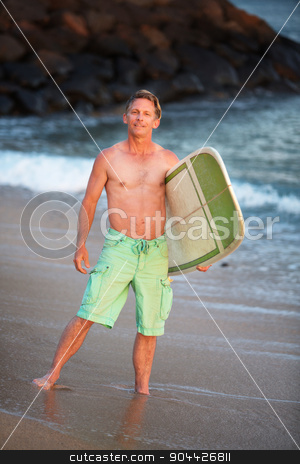 Surfer in Green Shorts with Surfboard stock photo, Happy male surfer standing on Maui waterfront  by Scott Griessel
