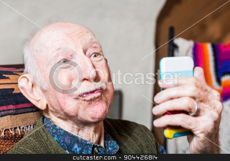 Older Gentleman with Smartphone stock photo, Older man looking at camera while taking silly face selfie by Scott Griessel