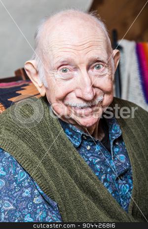 Elder Man Smiling at Camera stock photo, Elder man smiling at camera seated in his livingroom by Scott Griessel