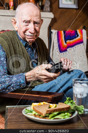 Older Gentleman with Sandwich stock photo, Older gentleman looking unhappily at a sandwich by Scott Griessel