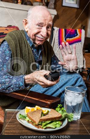 Elderly Man with Sandwich stock photo, Elderly man alone in green vest with sandwich by Scott Griessel