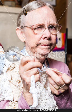 Suspicious Old Woman in Livingroom stock photo, Suspicious old woman in pink sweater crocheting at home by Scott Griessel