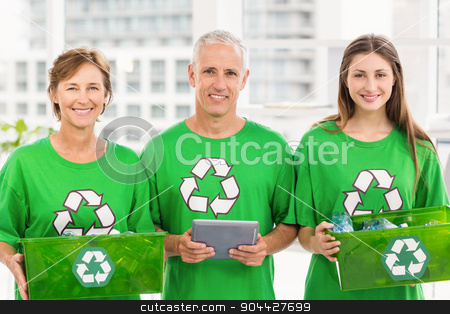 Smiling eco-minded colleagues with recycling boxes stock photo, Portrait of smiling eco-minded colleagues with recycling boxes in the office by Wavebreak Media