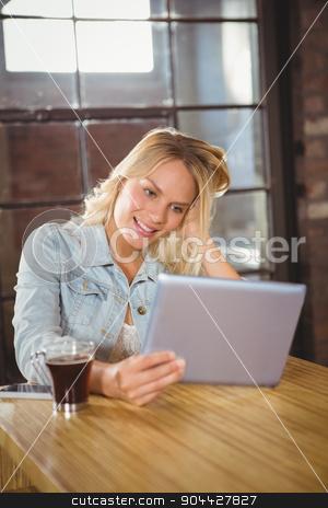 Smiling blonde holding tablet computer stock photo, Smiling blonde holding tablet computer at coffee shop by Wavebreak Media