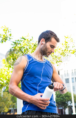 Handsome athlete with bottle checking heart rate watch stock photo, Handsome athlete with bottle checking heart rate watch in the city by Wavebreak Media