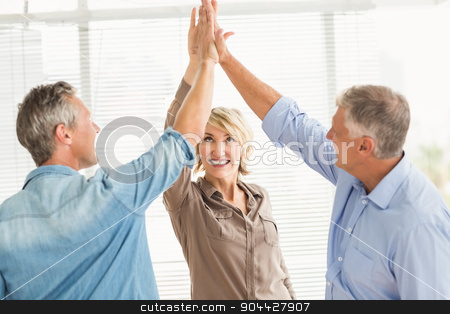 Smiling business colleagues giving high-five stock photo, Three smiling business colleagues giving high-five at the office by Wavebreak Media