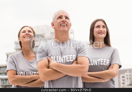 Smiling volunteers looking up stock photo, Smiling volunteers looking up on roof of building  by Wavebreak Media