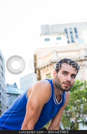 Determined handsome athlete looking away stock photo, Determined handsome athlete looking away in the city by Wavebreak Media