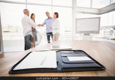 Planner in front of handshaking business people stock photo, Planner in front of handshaking business people in the office by Wavebreak Media