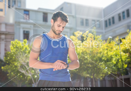 Focused handsome athlete setting heart rate watch stock photo, Focused handsome athlete setting heart rate watch in the city by Wavebreak Media