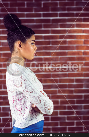 Close up of a serious woman looking away stock photo, Close up of a serious woman looking away on a brick wall by Wavebreak Media