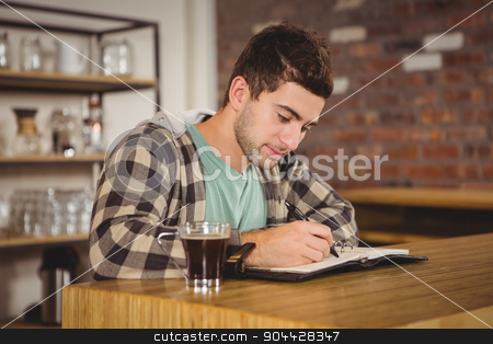 Hipster having coffee and writing in planner stock photo, Hipster having coffee and writing in planner at coffee shop by Wavebreak Media