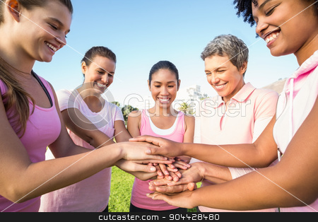 Women wearing pink for breast cancer and putting hands together stock photo, Women wearing pink for breast cancer and putting hands together in parkland by Wavebreak Media