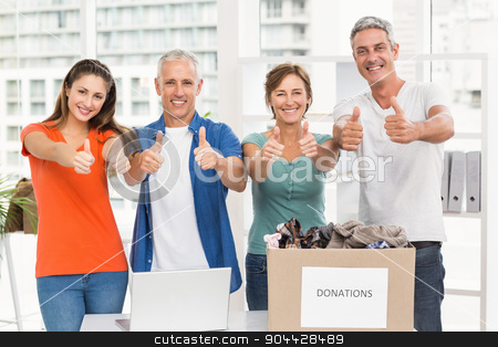 Casual business people donating and doing thumbs up stock photo, Portrait of casual business people donating and doing thumbs up in the office by Wavebreak Media