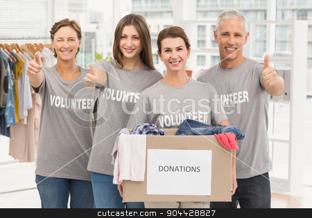 Smiling volunteers with donation box stock photo, Portrait of smiling volunteers with donation box in the office by Wavebreak Media