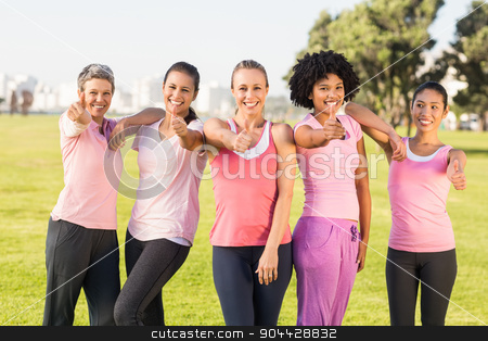 Smiling women wearing pink for breast cancer and doing thumbs up stock photo, Portrait of smiling women wearing pink for breast cancer and doing thumbs up in parkland by Wavebreak Media