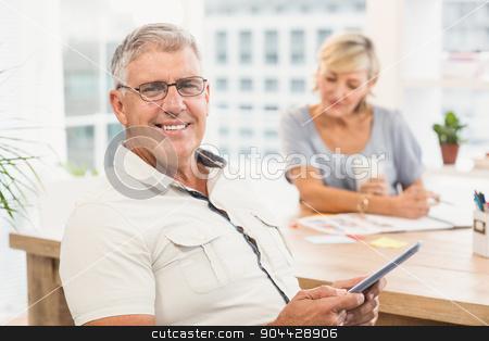 Smiling businessman holding a digital tablet stock photo, Portrait of a businessman holding a digital tablet at office by Wavebreak Media