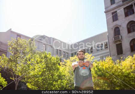 Handsome athlete lifting kettle bell stock photo, Handsome athlete lifting kettle bell in the city by Wavebreak Media